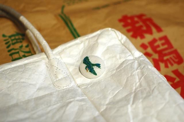 タイベックのバッグに詩集のブローチ